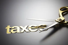 Recuce tax. Scissors and the alphabet TAXES Stock Image