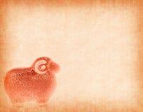 Recuerdo de cerámica de la cabra en el papel rojo Foto de archivo