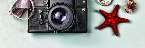 Recuerdos antiguos de la cámara, del compás y del mar en un fondo azul Foto de archivo libre de regalías