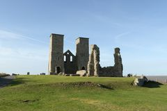 Reculver towers roman saxon shore fort and remains of 12th century church. Reculver towers roman saxon shore fort and remains of 12th century church undercut by Royalty Free Stock Image