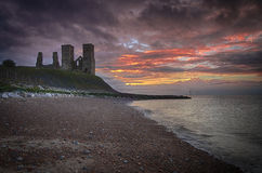 Reculver Towers. At sunset with the beach and sea in the foreground Stock Images