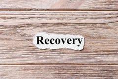 Recuperación de la palabra en el papel Concepto Palabras de la recuperación en un fondo de madera fotografía de archivo libre de regalías