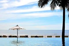 Recurso da parte dianteira da praia da piscina do sol da areia do mar em Tailândia foto de stock
