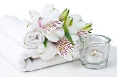 Recursos para termas, a toalha branca, a vela e a flor Foto de Stock Royalty Free