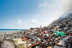 Recuse na descarga de lixo completamente do fumo, da maca, de garrafas plásticas, de desperdícios e de lixo na ilha tropical imagem de stock
