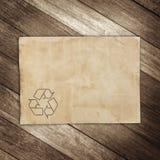 Recyc tecken på bakgrund för brunt papper för textur Arkivbilder