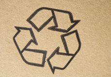 Recyclable. Universal symbol, printed on brown cardboard Stock Photography