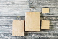 Recyclable concept. Blank brown paper shopping bags hanging on wooden wall. Recyclable concept. Mock up Royalty Free Stock Photo