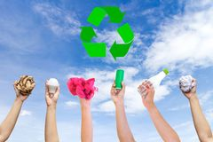 Recyclable hand hold show symbol plastic bottle used paper canned light bulb. A sky background Stock Photo