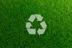 Recyclable Symbol a green grass background. Recyclable Symbol a green on grass background Stock Images