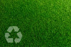 Recyclable Symbol a green grass background. Recyclable Symbol a green on grass background Stock Photos