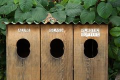 Recycle. Horizontal image of natural wood recycle bins for aluminum, glass and plastic bottles - with sparrows perched on the roof Stock Images