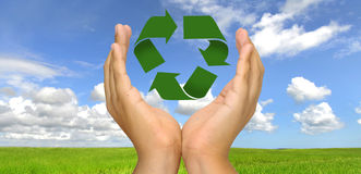 Recycle. Hands with recycle symbol over a green field Stock Photography