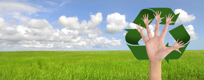 Recycle. Tree made of hands and recycle symbol over a green field Stock Images