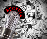 Recycle. Message on a vintage microphone with shredded paper in the background.  This image conveys the concept of the importance of recycling in today's Royalty Free Stock Images