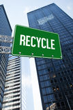 Recycle against low angle view of skyscrapers. The word recycle and green billboard sign against low angle view of skyscrapers Royalty Free Stock Photo