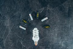 Recycle, alternative energy concept with led lamp and batteries. Hazardous waste on a black stone background with space for text.  royalty free stock photography