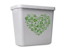 Recycle bin. Empty gray plastic recycle bin with green recycle pictograms arranged into heart shape over white background royalty free stock image