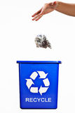 Recycle bin. Throwing some trash to a blue recycle bin royalty free stock photo