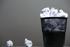 Recycle bin filled with crumpled papers. Gray background Royalty Free Stock Photos