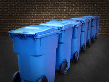 Recycle Bins. In a group made of commercial size blue plastic containers in a city street back alley against a brick wall as a conservation and recycling symbol Royalty Free Stock Photography