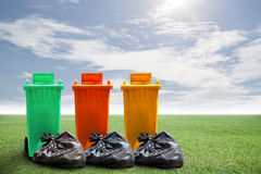 Recycle bins and bag garbage on green grass and sky background , Stock Photo