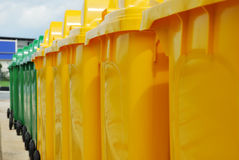 Recycle bins in a group made of commercial size yellow and green. Plastic containers Stock Photos
