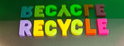 Recycle: go green. Text ' recycle ' in colorful uppercase letters with reflection in a green mirror surface showing the word in duplicate Royalty Free Stock Image