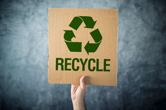 RECYCLE. Man holding cardboard with Recycle symbol printed Stock Photography
