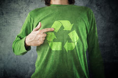 RECYCLE. Man pointing to recycling symbol printed on his shirt. Man pointing to RECYCLE symbol printed on his shirt, environment preservation activist Stock Photo