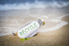 Recycle message in a bottle. Recycle written as massage in a bottle washed ashore and layed on the sand Stock Photos