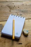 Recycle notebook , pencil and eraser. Notebook recycling and pencil on wooden Royalty Free Stock Image