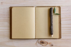 Recycle notebook with wooden pencil on wooden desk Stock Image