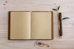 Recycle notebook with wooden pencil on wooden desk Royalty Free Stock Image