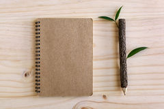 Recycle notebook with wooden pencil on wooden desk Royalty Free Stock Images