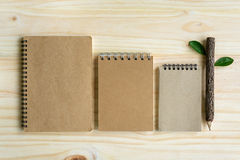 Recycle notebook with wooden pencil on wooden desk Stock Photos