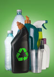 Recycle the plastics. Set of different plastic containers on green background with the recycle sign on the front one Royalty Free Stock Photos