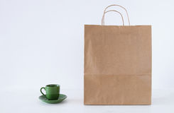 Recycle shopping bag next to cup of coffee on the table and white background. Image of empty recycle shopping bag next to cup of coffee on the table and white Royalty Free Stock Photo
