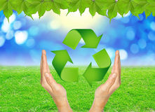 RECYCLE sign in hands against green spring background. Stock Photography