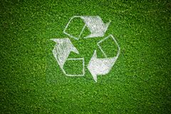 Recycle Sign over Green Grass. White Recycle Sign over Natural Green Grass background Royalty Free Stock Photos