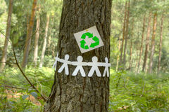 Recycle sign with paper men on a tree Stock Images