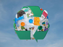 Recycle sphere. Sphere formed from assorted domestic waste wrapped around by green three arrow recycle symbol over blue sky Royalty Free Stock Photo