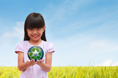 Recycle symbol. Smiling little girl holding earth with recycle symbol Royalty Free Stock Images