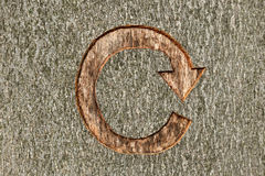 Recycle symbol carved into a tree. The recycle symbol carved into a tree in managed woodland. This tree was marked to be cut down as part of a forestry clearing Stock Photo
