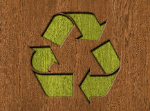 Recycle symbol. Carved in wood background Stock Image