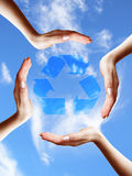 Recycle symbol in a hands circle on sky background Royalty Free Stock Photos