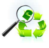 Recycle symbol under magnifying glass Royalty Free Stock Photos