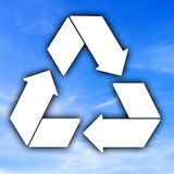 Recycle to save the planet. A conceptual image with a clean white recycle icon against a fresh blue summer sky Stock Images