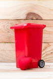 Recycle trash bin with heart on wood background Royalty Free Stock Photo