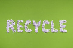 Recycle. Word made from heap of shredded white paper over green Stock Photography
